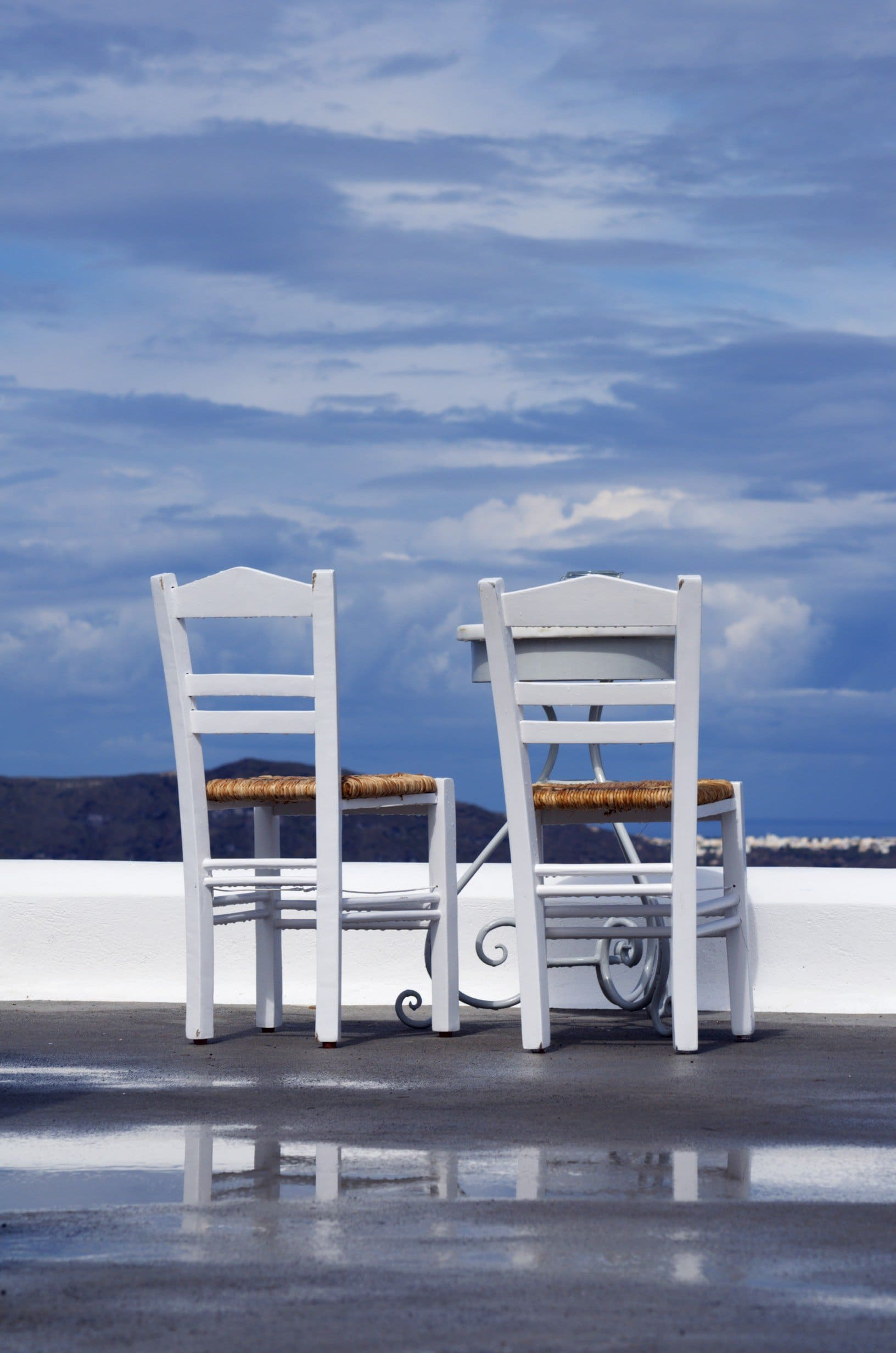 griechische Stühle auf Terrasse nach Regen