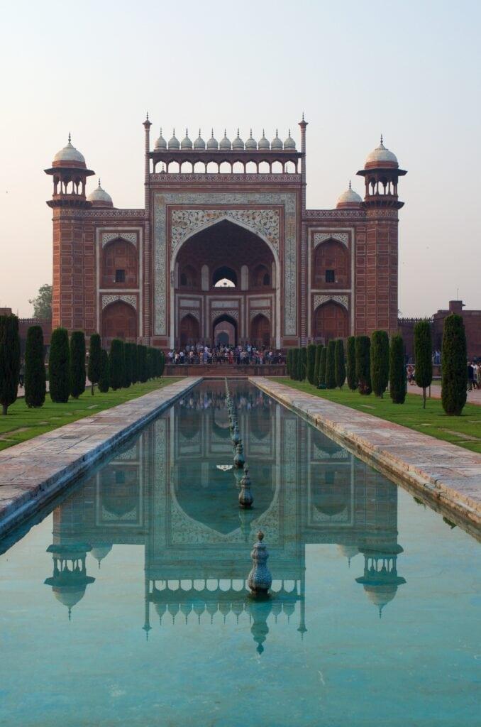 Eingangstor zum Taj Mahal spiegelt sich im Wasser