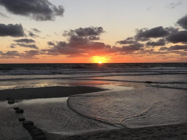 Sonne versinkt im Meer bei Westerland