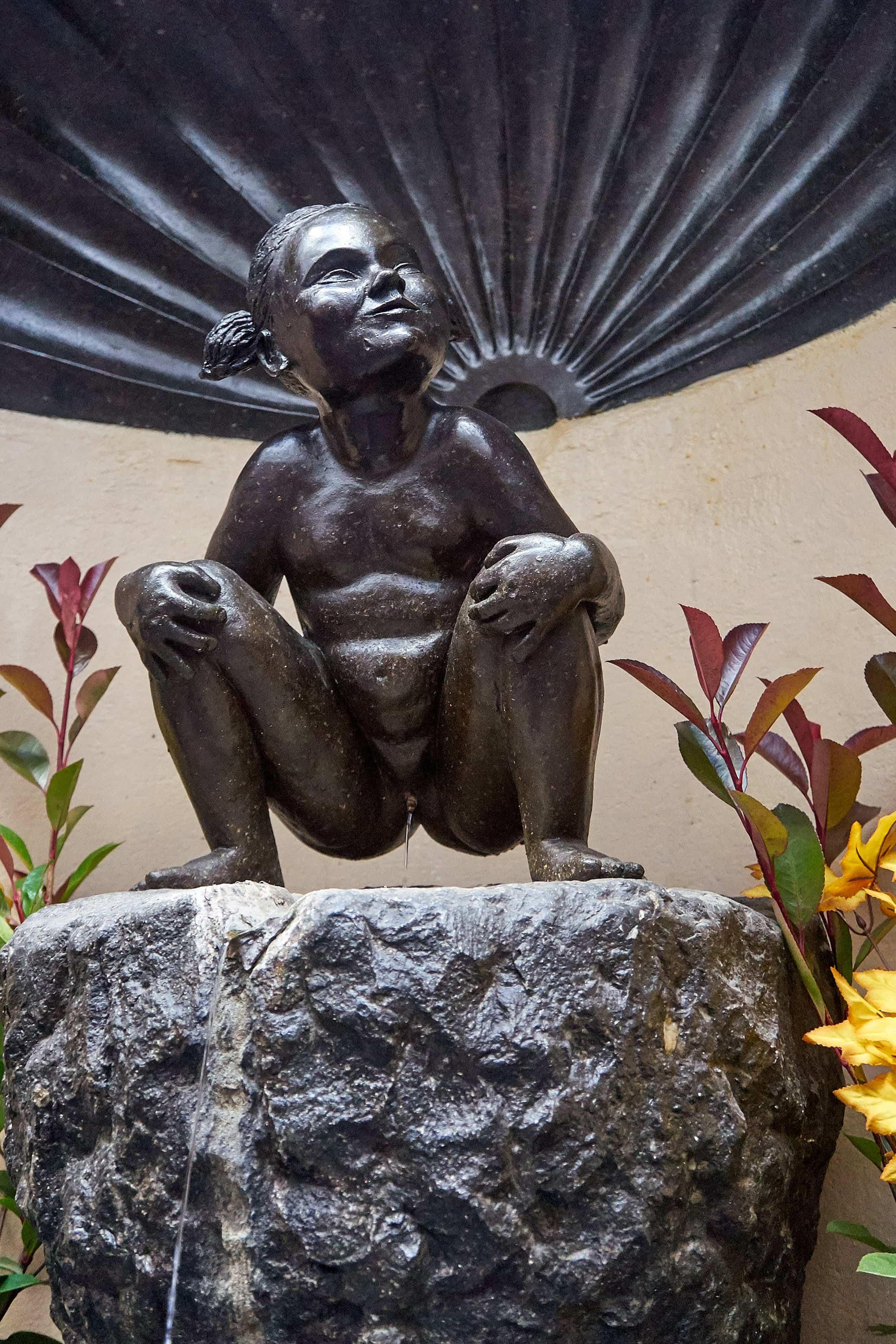 Brunnen mit Brozeskulptur eines urinierenden Mädchens