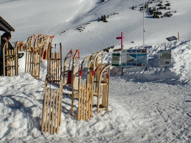 Wegweiser und Schlitten vor der Bergstation